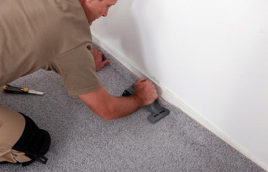 Ein Arbeiter der Teppich verlegt