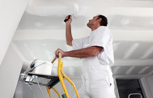 Ein Maler auf einer Leiter streicht die Decke