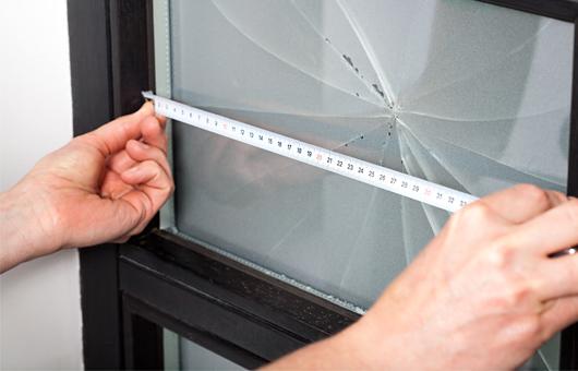Mit einem Zollstock wird an einem kaputten Fenster Maß genommen
