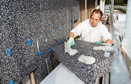 Ein Maler verklebt Wärme-Dämm-Verbundplatten
